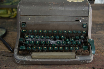 close up of vintage damaged Typewriter on wooden table.