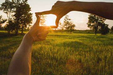Close up of hands making frame gesture. Close up of woman hands making frame gesture with sunset.