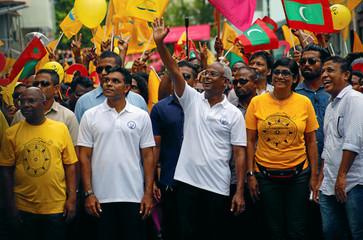 Ibrahim Mohamed Solih, Maldivian presidential candidate backed by the opposition coalition, waves as he stands next to his supporters during the final campaign rally ahead of the presidential election in Male