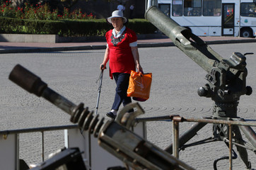 A man looks at weapons captured from militants in Syria, during an exhibition in Sevastopol