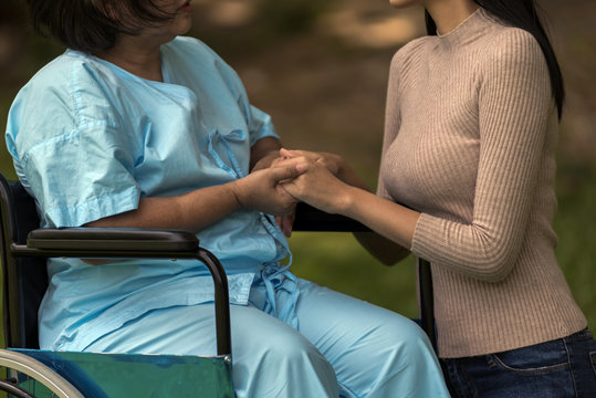 Closeup the Elderly female hand holding hand of young caregiver at nursing home.