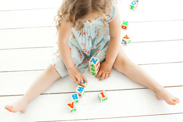 Unrecognizable little girl playing with abc cubes indoors