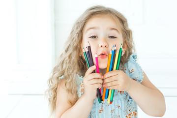 Portrait of cutew little girl holding pencils