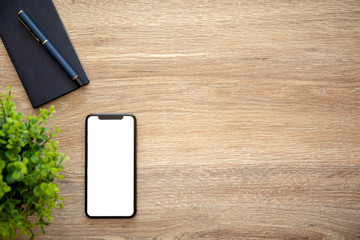 phone with isolated screen on wooden table with a notebook