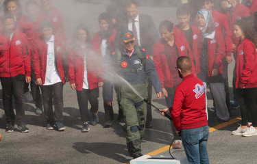 Turkish President Tayyip Erdogan in military pilot outfit arrives to Teknofest airshow as a volunteer sprays rose essence at a new airport under construction in Istanbul