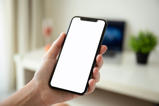 woman hand holding phone with isolated screen in room house