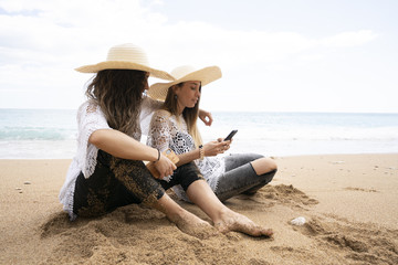 Girls using mobile phone in beach