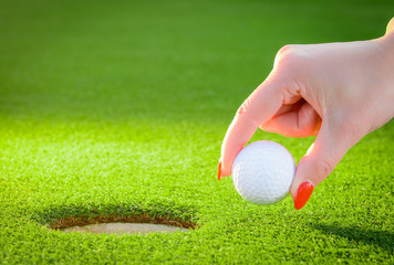 golfball regarded a woman's hand to the hole