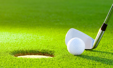golf ball from the hole with the putter on golf turf