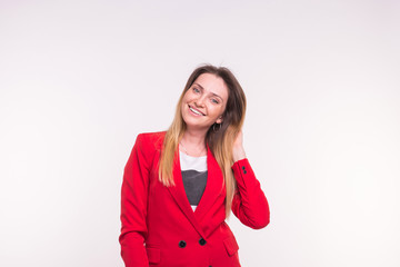 Portrait of fashionable young white freckled woman in red suit on white background