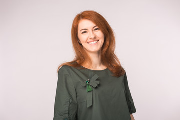 Fashion and people concept - Portrait of happy ginger woman smiling looking at camera over white background