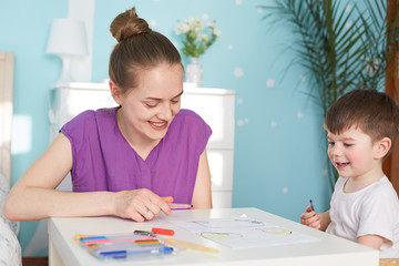 Beautiful housewife in casual purple t shirt spends free time with her little son, use colorful markers for drawing picture, pose against cozy domestic interior. Childhood and motherhood concept