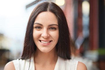 Headshot of pleasant looking charming smiling young woman with healthy skin, dark hair, being in good mood, shows her natural beauty, poses outdoor against blurred background. Happiness concept