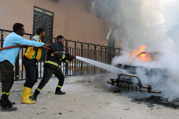 Fire fighters attempt to extinguish a burning car after an explosion in Mogadishu