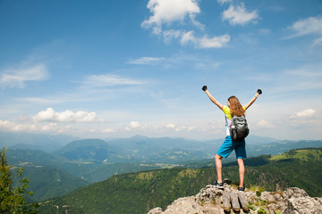 Active woman gesturing success after climbing a mountain