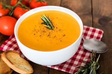 Squash Soup with Rosemary on rustic wooden table.  Autumn Pumpkin cream-soup in a white bowl  with croutons. Top view.
