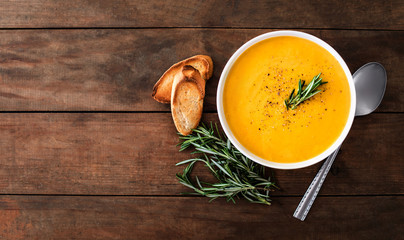 Pumpkin and carrot  Cream soup on rustic wooden table. Autumn Pumpkin cream-soup with rosemary herb and croutons. Top view. Copy space.