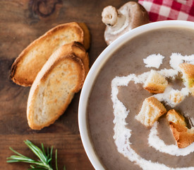 Mushroom cream soup with herbs and spices. Homemade, country styled chanterelle Cream-soup on wooden table.