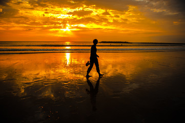 A person walks across a shimmering beach at sunset.