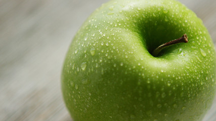 Closeup fresh healthy green apple with water condensation drops on table