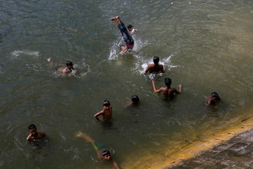 Children swim in a lake on a hot summer day in Dhaka