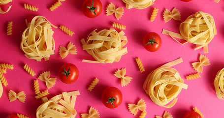 Flat lay of abstract arrangement of uncooked pasta and macaroni with bright red tomatoes on pink background