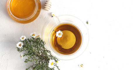 From above view of glass cup of tea and bowl of honey decorated with flowers of camomile on white background