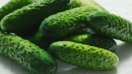 Closeup of textured pimply green cucumbers lying in small heap in soft daylight