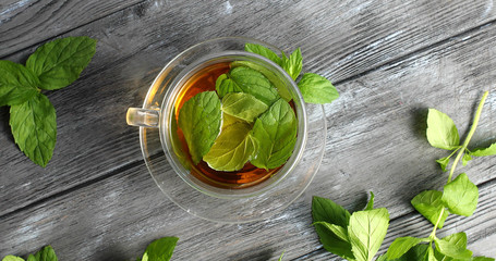 Top view of glass cup with fresh herbal tea and mint leaves on gray wooden table