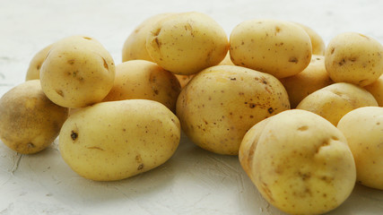 Closeup shot of pile of unpeeled clean potatoes composed on white surface in daylight