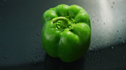 Closeup of shiny green bell pepper with drops of water shining on glass wet surface