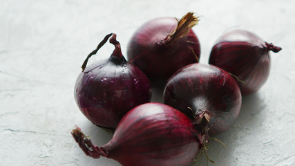 Closeup shot of unpeeled bulbs of red onion lying on white table surface in daylight