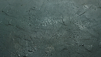 Abstract background of rough gray stone surface covered with water drops shining in daylight