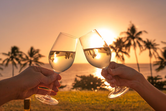 Couple cheers with wine glasses in a beautiful sunset beach setting.