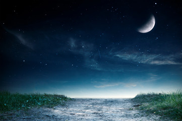 Magic landscape with road and grass over night sky. Moon on this image furnished by NASA