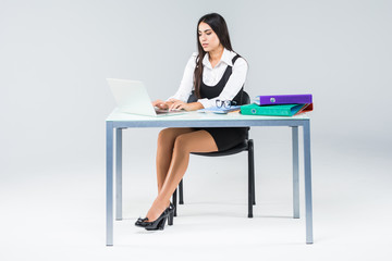 Beautiful business woman smile sitting at the desk working using laptop looking at screen typing on laptop isolated over white background