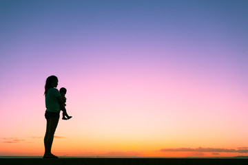 Silhouette of mother holding her little baby girl watching the sunset. Motherhood, parenting concepts.