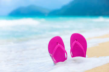 Pair of slippers on a white sandy beach. Beach vacation background.