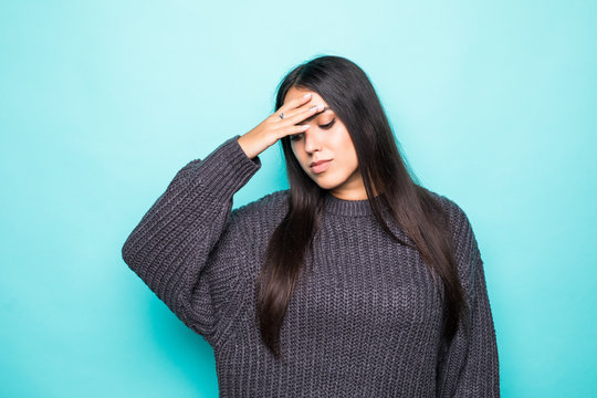 Young beautiful woman wearing winter sweater over isolated blue background suffering from headache desperate and stressed because pain and migraine. Hands on head.
