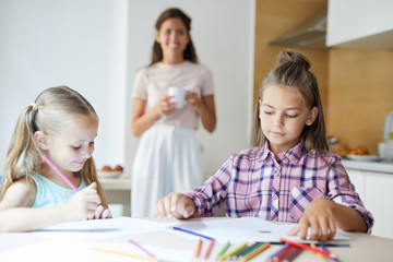 Youthful girls with crayons drawing pictures while sitting by table in the kitchen with their mom on background