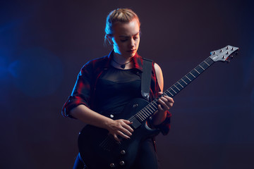 Blonde woman play guitar on stage, red, blue light dark scene