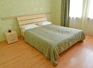 Double bed in the hotel room of economy class