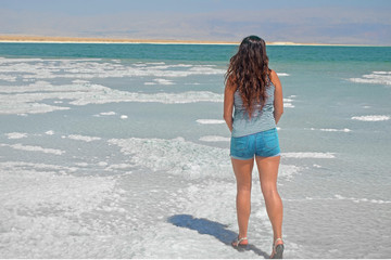 young girl looking into the distance to the mountains. brunette walks on the islands from salt in the dead sea, Israel