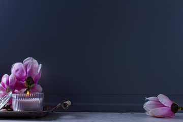 Gray room interior close up decor with burning candle and fresh magnolia flowers with copy space on the wall