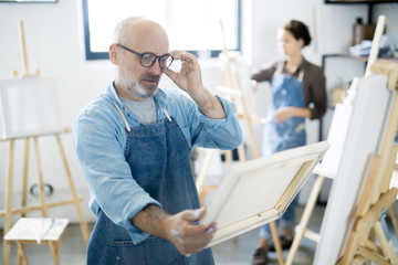 Serious man in eyeglasses and workwear looking at painting in his hands while standing by easel in studio