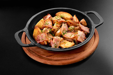 American potatoes with salt pepper parsley and cumin fried bacon in roasted black pan on wooden on black background