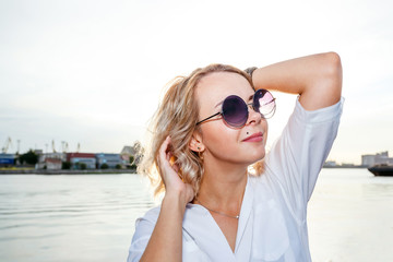 young beautiful blonde girl in sunglasses on a sunny afternoon sitting on the river bank in the city
