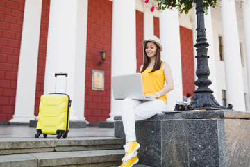 Pensive traveler tourist woman in casual clothes, hat with suitcase sitting using working on laptop pc computer in city outdoor. Girl traveling abroad on weekends getaway. Tourism journey lifestyle.