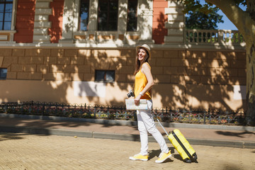Joyful traveler tourist woman in yellow summer casual clothes hat with suitcase city map walking in city outdoor. Girl traveling abroad to travel on weekend getaway. Tourism journey lifestyle concept.