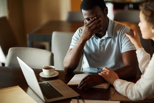 Young businessman in trouble sharing his problem with female colleague who comforting him
